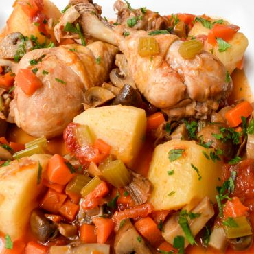 Chicken drumsticks with mushrooms, potatoes and tomatoes